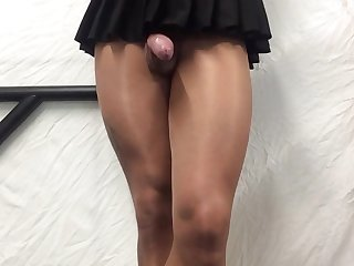 Tan pantyhose showing cock under pleated mini skirt .
